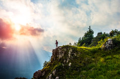 Over the top. A young girl arrives on the top of the mountain Stock Photography