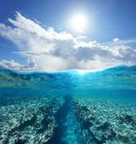 Over under seascape sunlight with reef underwater. Over and under water surface seascape, sunlight with cloudy blue sky and split by waterline a natural trench Stock Photo