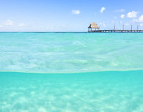 Over under shallow tropical sea with wooden dock Royalty Free Stock Photos