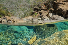 Over underwater river rocks and stack of pebbles. Over and under the water in a river with rocks on the riverbed underwater and a stack of pebbles above the Royalty Free Stock Photo