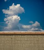 Over the Wall. View over a drab brick wall to a bright blue sky beyond Stock Photo