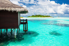 Over water bungalow with steps into amazing blue lagoon with isl. And in distance Stock Photography