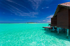 Over water bungalow with steps into blue lagoon. Over water bungalow with steps into amazing blue lagoon Stock Image