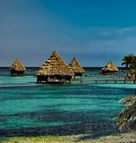 The over-water bungalows in Glover`s Atoll, Belize. Some of the thatched roofed bungalows, over blue-green waters in Glover`s Atoll, Belize royalty free stock image
