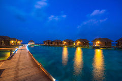 Over water bungalows with steps into amazing green lagoon. Maldives Stock Photography