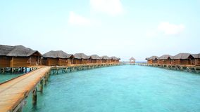 Over water bungalows with steps into amazing green lagoon. Maldives stock footage