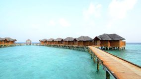 Over water bungalows with steps into amazing green lagoon. Maldives stock video footage