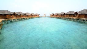 Over water bungalows with steps into amazing green lagoon. Maldives stock video