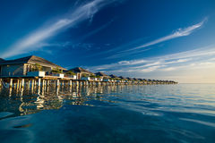 Over water villas in Maldives reflected in blue lagoon Royalty Free Stock Photo