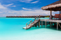 Over waterbungalow met stappen in blauwe lagune Stock Foto's