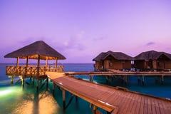 Over waterbungalowwen met stappen in verbazende groene lagune stock afbeelding