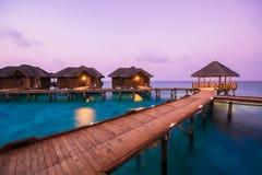 Over waterbungalowwen met stappen in verbazende groene lagune stock foto's