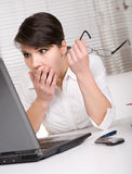 Over-worked. Young adult over-worked woman at desk royalty free stock image