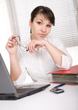 Over-worked. Young adult over-worked woman at desk royalty free stock photography