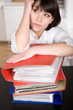 Over-worked. Young adult over-worked woman at desk royalty free stock photos