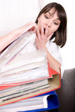 Over-worked. Young adult over-worked woman at desk Stock Images