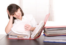 Over-worked. Young adult over-worked woman at desk Stock Photo