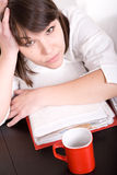 Over-worked. Young adult over-worked woman at desk Royalty Free Stock Photo