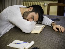Tired young man falling asleep reading book. Over-worked, tired young man at home sleeping instead of working or studying, resting head over book. Tired male royalty free stock photography
