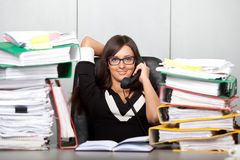 Over-worked woman in office, speaking on phone. Stock Image