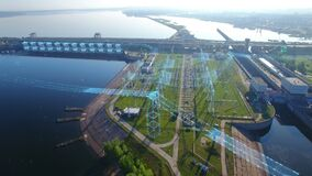 Overall aerial orbit view a high voltage electric power tower, hydroelectric power station and electric substation with