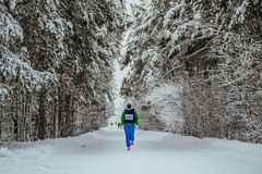 Overall plan girl athlete running in winter forest Stock Image