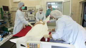 A group of surgeons shift the patient after surgery to a bed for transportation. Overall plan. A group of surgeons in surgical clothing shift the patient after stock footage