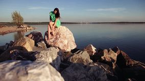 Overall plan. sexy girl figure posing on the rocks by the ocean stock footage