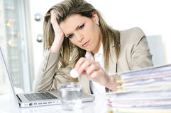 Overbooked. Young woman stressed at work, taking an aspirin cahet Stock Image
