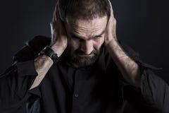 Overburdened frustró los oídos de la cubierta del hombre y parecer desesperada Imagenes de archivo
