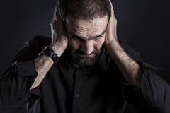Overburdened frustrated man covering ears and looking despaired. Stock Images