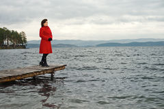 Overcast day. Beauty mature woman in red topcoat, outdoor on water moorage for boat, in autumn cold overcast day Royalty Free Stock Photos