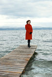 Overcast day. Beauty mature woman in red topcoat, outdoor on water moorage for boat, in autumn cold overcast day Royalty Free Stock Image