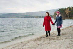 Overcast day. Beauty mature women in red topcoat with young daughter, walking outdoor on water moorage for boat, in autumn cold overcast day Royalty Free Stock Images