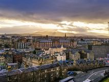 Overcast Day in Edinburgh. With the sun peaking though the clouds with the old city and rolling hills in the back royalty free stock photos