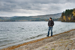 Overcast day. Young guy outdoor on water moorage for boat, in autumn cold overcast day royalty free stock photo