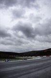 Overcast racing circuit. A racing circuit with a lone sports car under an overcast sky Royalty Free Stock Photography