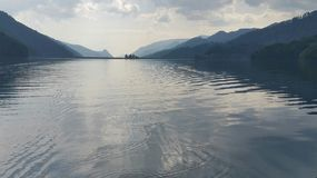 Overcast and rainy weather on the lake. Mountain lake overcast atmosphere with dimmed sunlight and small waves Stock Image