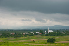 Overcast sky. Church in the village. Agricultural field. Stock Image