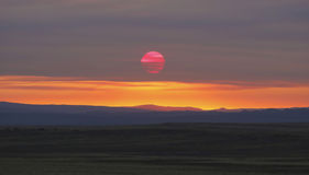 An Overcast Sky Filters the Rising Sun. An Overcast Sky Filters the Red Rising Sun Royalty Free Stock Photo