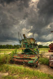 Overcast sky over abandoned farm equipment Royalty Free Stock Images