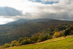 Overcast sky over meadow and forest in autumn colors, mountain Goc Royalty Free Stock Photo