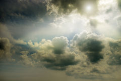 Overcast sky and the sun behind cumulus clouds. Stock Images