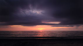 Overcast Sunset on the Ocean Horizon. Ominous, overcast clouds over an ocean sunset, sun disappearing on the horizon Royalty Free Stock Images