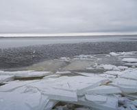 Overcast Winter Lake. Moody overcast day over Lake Winnebago. The lake is again mostly open water with piles of ice on the shore royalty free stock image