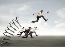 Overcome and achieve success. Businessman jumping on a spring during a race with opponents Stock Photography