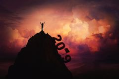 2019 overcome. As a businessman lift hands up on the top of mountain reaching the finish flag. New year celebrate win and success over sunset background. Goal royalty free stock image