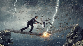 Overcome fear of failure . Mixed media. Businessman with umbrella and suitcase walking on wooden log. Mixed media Stock Photography