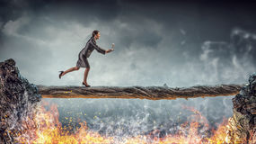 Overcome fear of failure . Mixed media. Young successful businesswoman jumping over gap. Risk and challenge concept Royalty Free Stock Photos