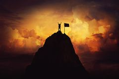 Overcome. Obstacle overcome as a woman raise hands up on the top of a mountain reaching the finish flag. Celebrate victory and success over sunset background stock photography
